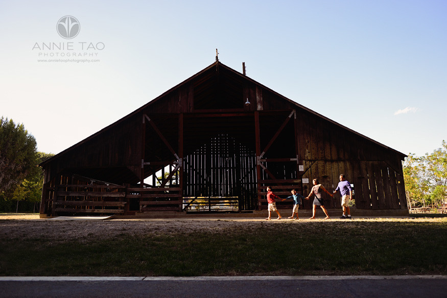 East-Bay-lifestyle-family-photography-family-holding-hands-and-walking-past-a-barn-in-a-streak-of-light