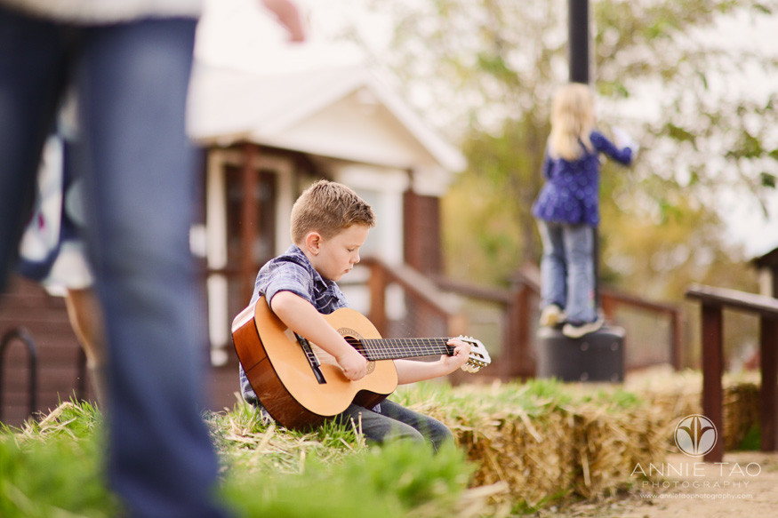 east-bay-lifestyle-children-photography-kids-climbing-on-haybales-while-boy-plays-guitar
