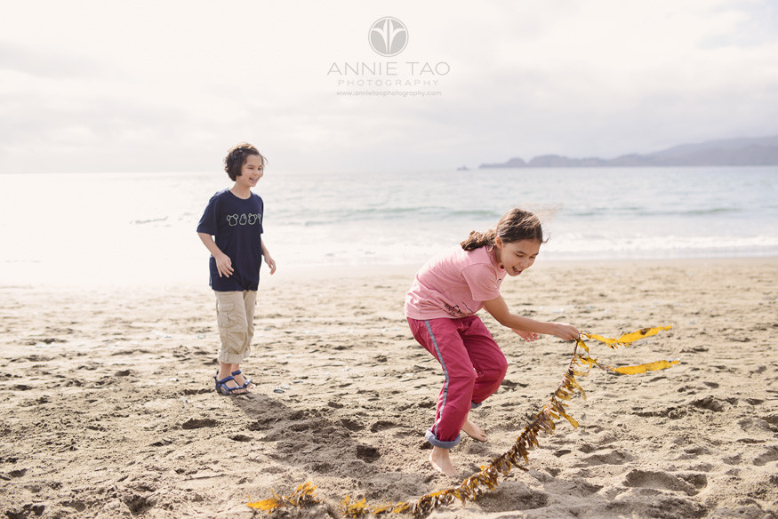 San-Francisco-lifestyle-family-beach-photography-sisters-playing-with-seaweed