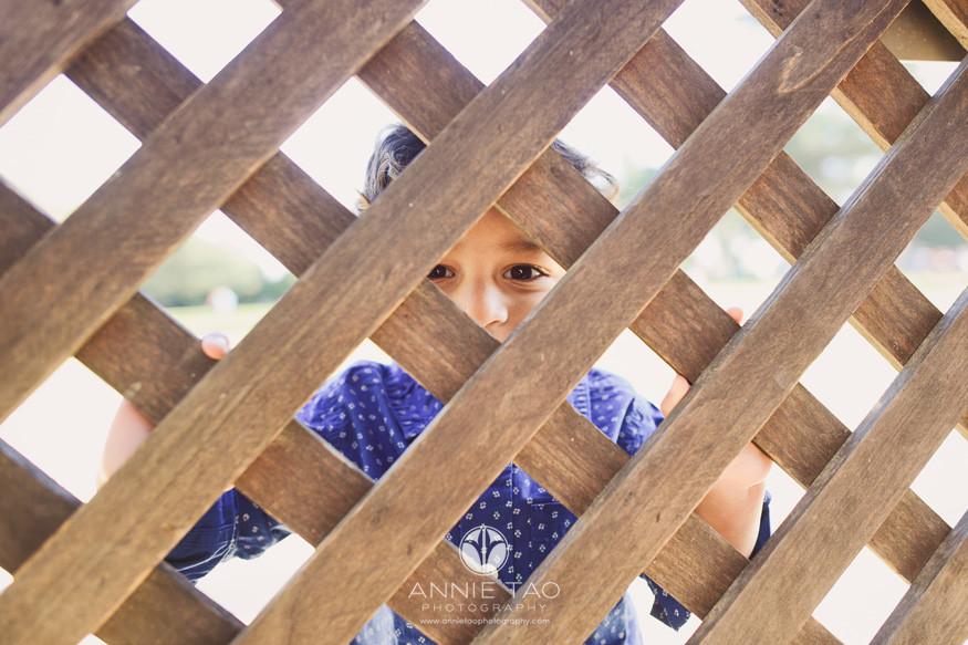 east-bay-lifestyle-children-photography-toddler-boy-peeking-through-wooden-fence