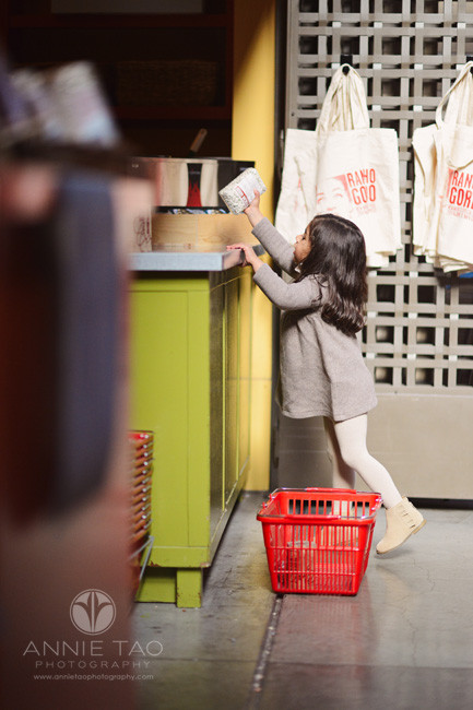san-francisco-lifestyle-children-photography-preschooler-girl-tippytoeing-to-place-items-by-cashier