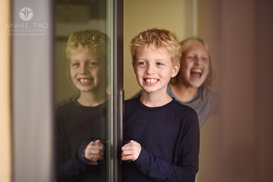 Bay-Area-lifestyle-children-photography-young-boy-opening-door-with-reflection-while-sister-photobombs