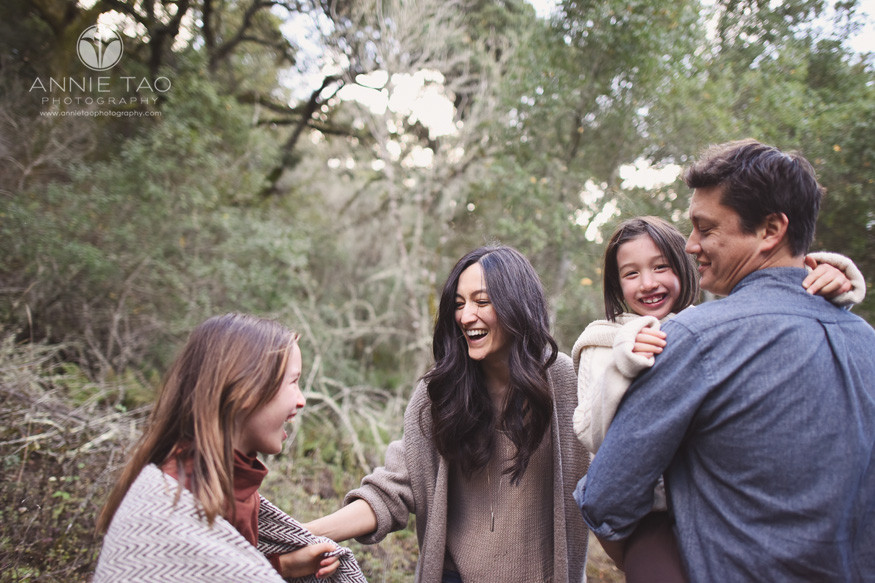 San-Francisco-bay-area-lifestyle-family-photography-laughing-while-one-girl-is-carried-and-one-girl-is-wrapped-in-blanket
