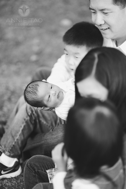 East-Bay-lifestyle-newborn-photography-baby-looking-around-while-family-looks-on-BxW