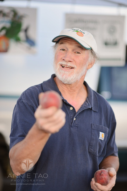 East-Bay-Commercial-Photography-farmer-holding-a-peach-at-Berkeley-farmers-market