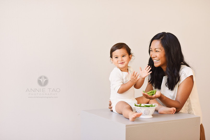 East-Bay-commercial-photography-happy-baby-clapping-while-mother-holds-snap-peas