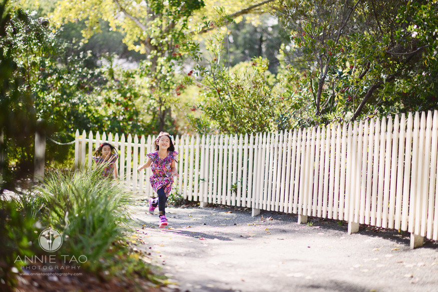 bay-area-lifestyle-children-photography-sisters-racing-on-path-by-a-white-fence