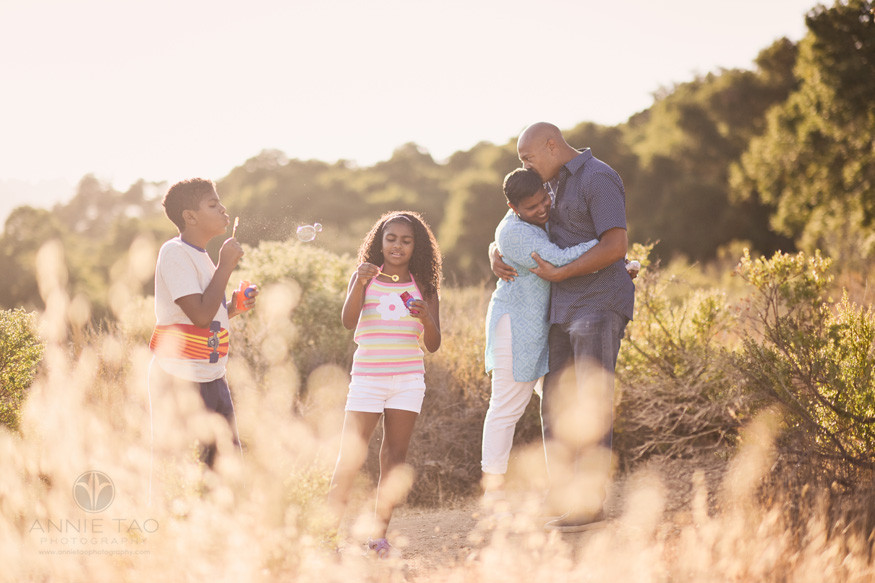 Bay-Area-lifestyle-family-photography-parents-having-a-moment-while-kids-play-with-bubbles-top-of-mountain-ridge