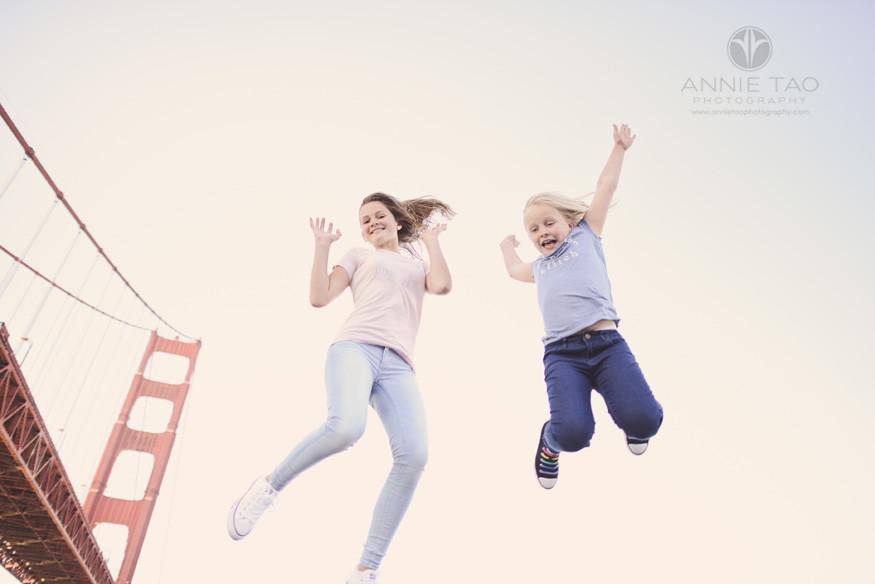 San-Francisco-lifestyle-children-photography-two-girls-jumping-next-to-Golden-Gate-Bridge