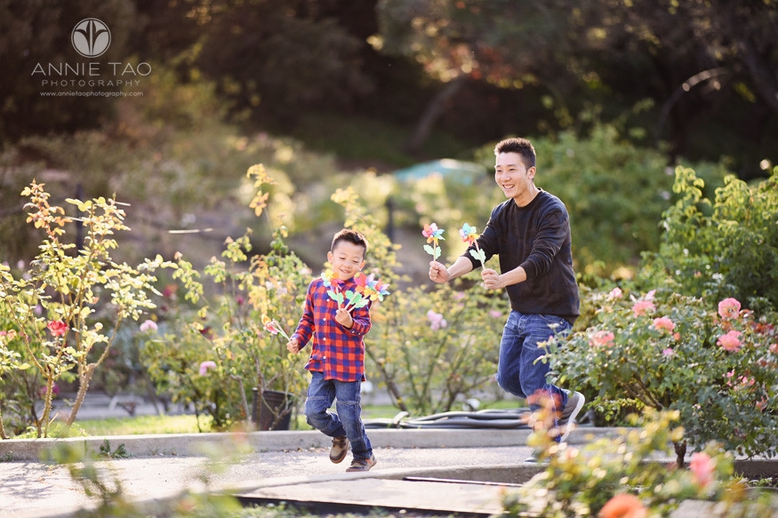 East-Bay-lifestyle-family-photography-father-chasing-young-son-in-rose-garden-with-flower-spinners