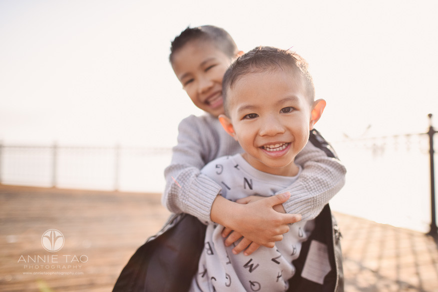 San-Francisco-lifestyle-children-photography-brothers-hugging-on-pier-with-wash-of-golden-sunlight