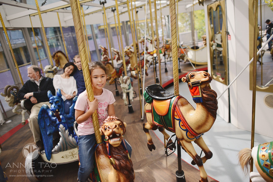San-Francisco-lifestyle-photography-girl-leaning-on-camel-with-parents-behind-her-at-creativity-carousel