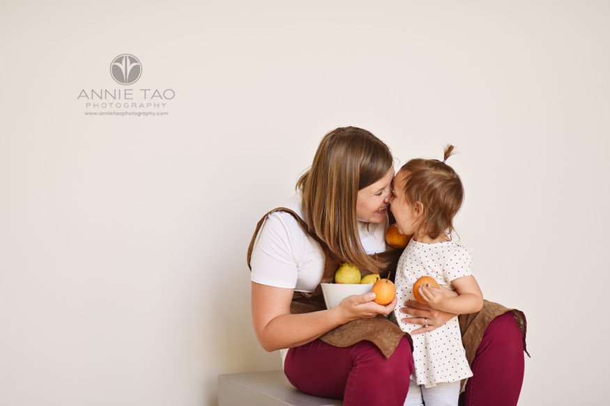 East-Bay-commercial-photography-mother-and-toddler-daughter-nuzzling-noses-while-holding-asian-pears