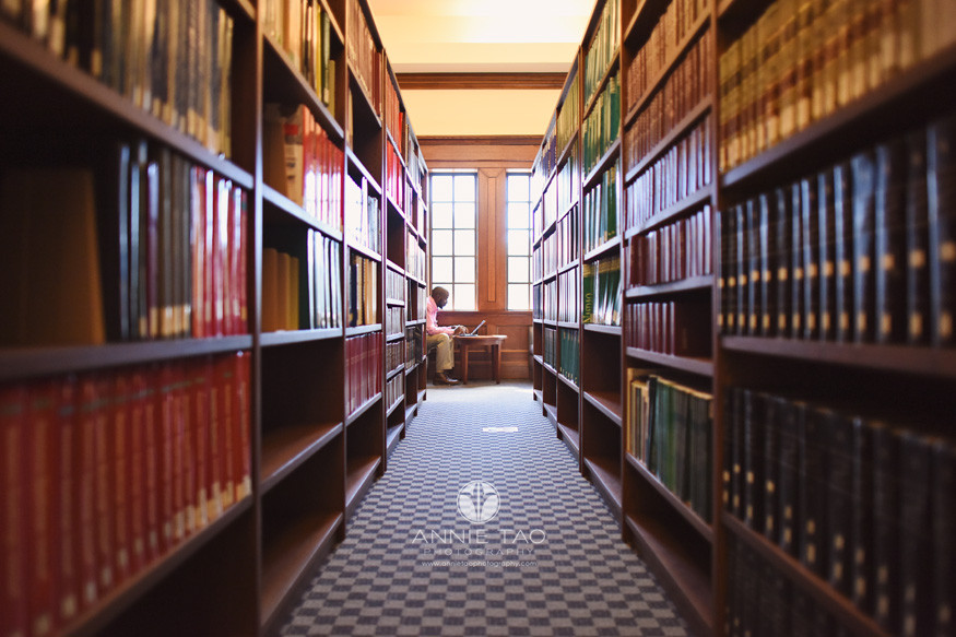 Commercial-Photography-Rice-Business-School-student-at-library-sitting-at-end-of-aisle