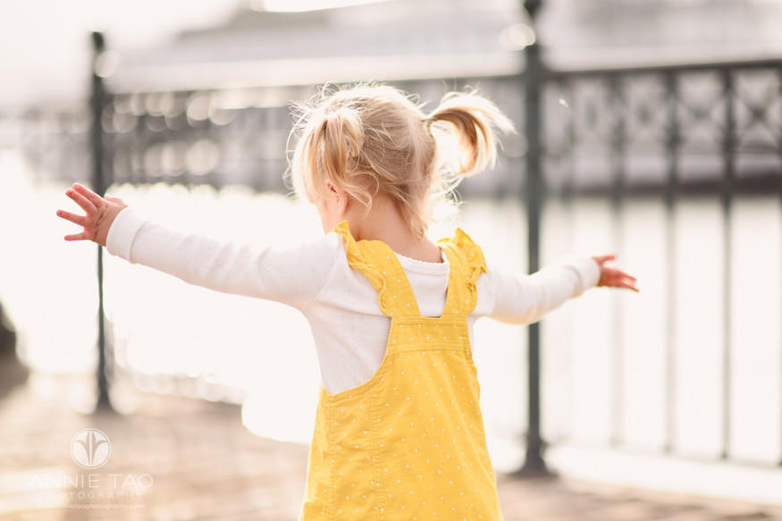 San-Francisco-lifestyle-children-photography-toddler-girl-with-pigtails-and-yellow-dress-flying-in-sunlight