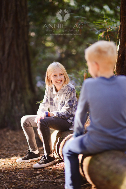 east-bay-lifestyle-children-photography-girl-talking-with-brother-on-log-in-woods