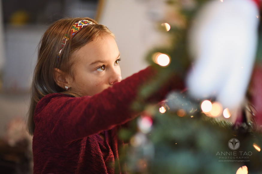 San-Francisco-lifestyle-children-photography-young-girl-hanging-Christmas-tree-ornament-focus-on-eyes