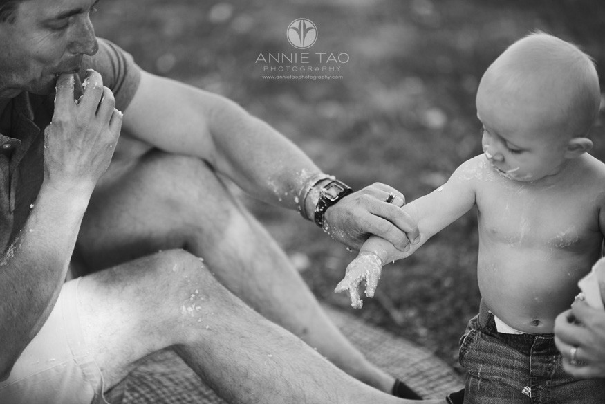 East-Bay-lifestyle-baby-photography-father-helping-baby-boy-after-cake-smash-BxW