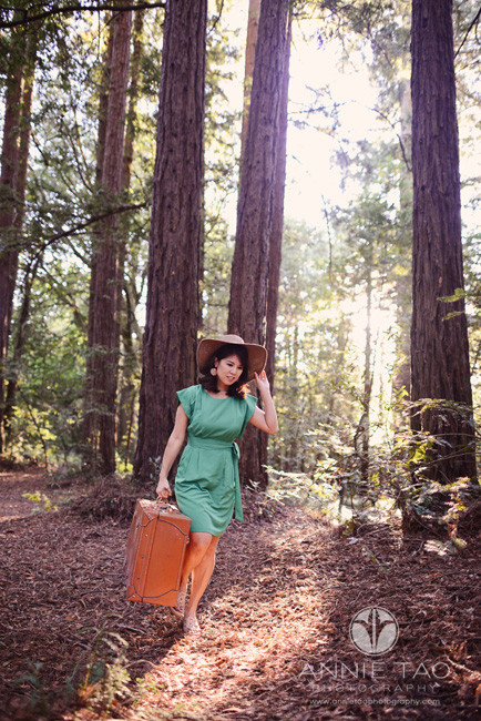 East-Bay-styled-photography-woman-holding-hat-and-suitcase-in-forest
