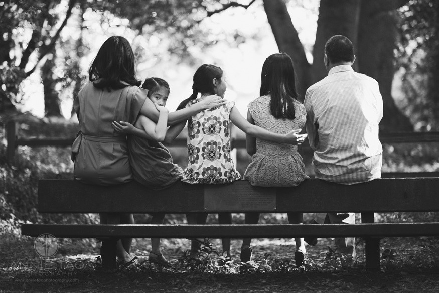 East-Bay-styled-family-photography-family-on-bench-with-little-one-peering-BxW