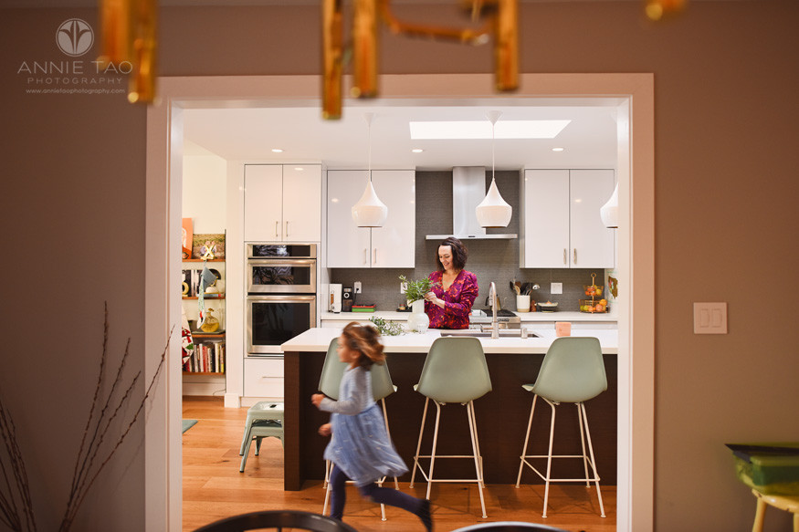 San-Francisco-lifestyle-home-family-photography-woman-putting-plants-in-vase-while-young-girl-runs-through-kitchen