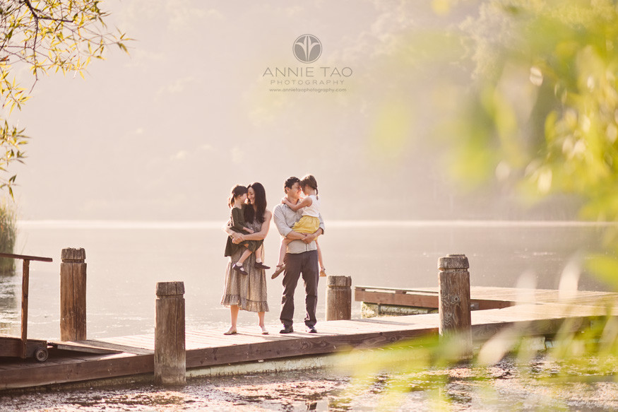 Bay-Area-lifestyle-family-photography-daughters-touching-heads-with-parents-on-dock-at-lake