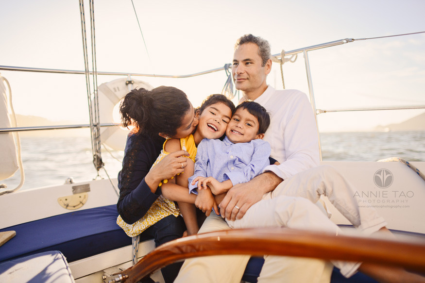 san-francisco-lifestyle-photography-family-cuddling-on-sailboat-by-golden-gate-bridge-at-sunset