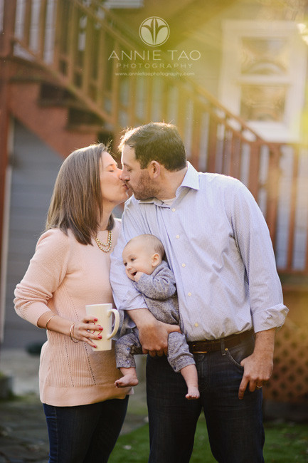 san-francisco-lifestyle-family-photography-parents-kissing-while-holding-baby-in-backyard