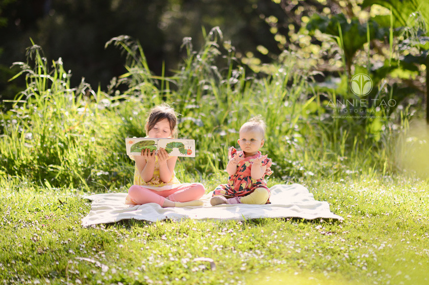 San-Francisco-lifestyle-children-photography-sister-reading-to-her-baby-sister-on-grass