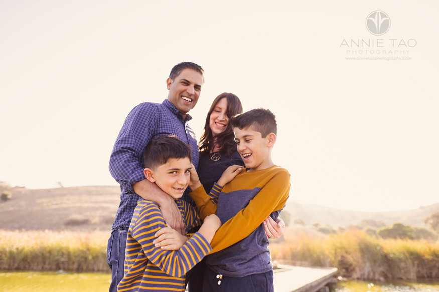 East-Bay-lifestyle-family-children-photography-brothers-playing-and-laughing-while-standing-with-parents-on-boardwalk