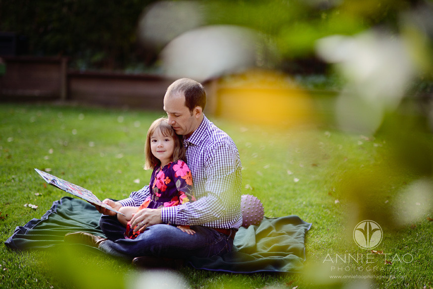 North-Bay-Marin-lifestyle-family-photography-toddler-girl-looks-up-as-father-reading-a-book