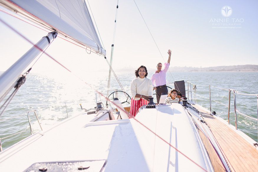 San-Francisco-lifestyle-family-photography-waving-at-friend-while-sailing-in-bay