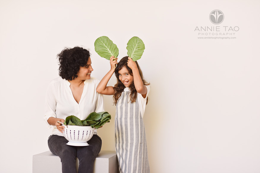 East-Bay-commercial-photography-mother-and-daughter-playing-with-collard-greens
