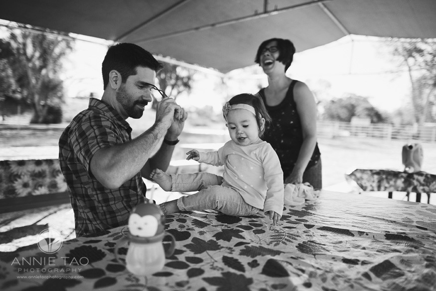 East-Bay-lifestyle-family-photograph-baby-sitting-on-picnic-table-with-parents-around-BxW