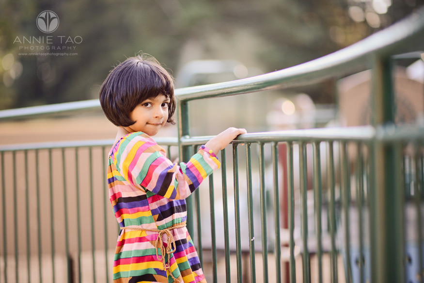 east-bay-lifestyle-children-photography-young-girl-wearing-stripes-and-standing-by-metal-fence