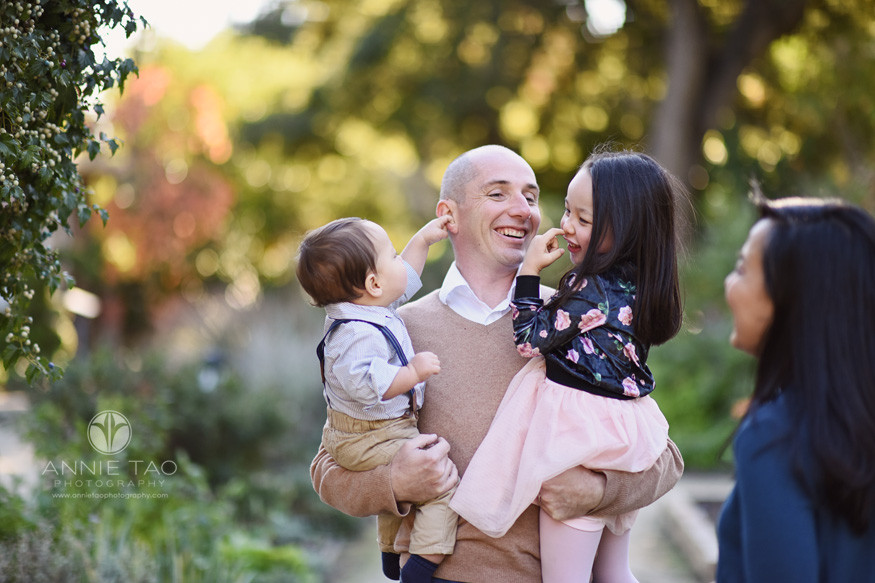 Bay-Area-lifestyle-family-photography-man-carrying-his-two-children-who-are-playing-with-his-face