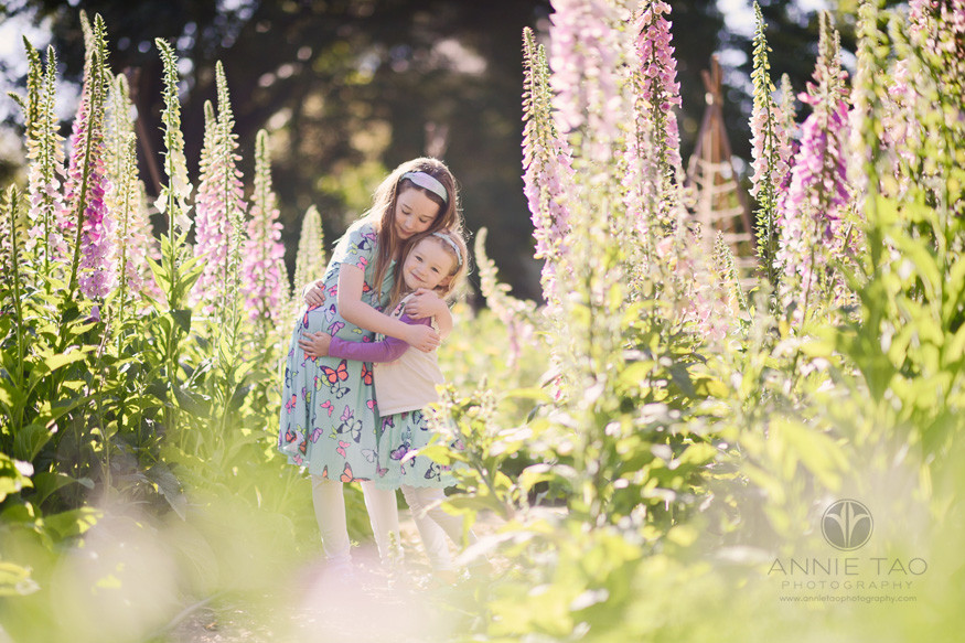 bay-area-lifestyle-children-photography-young-sisters-hugging-in-garden-on-sunny-day
