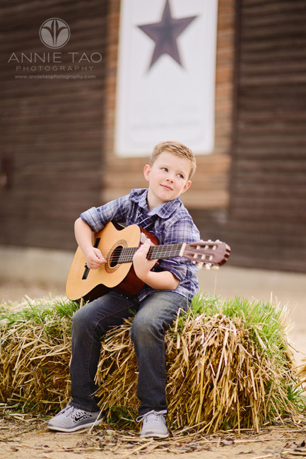 east-bay-lifestyle-children-photography-boy-playing-guitar-on-haybale