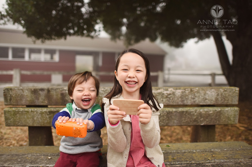 San-Francisco-Bay-Area-lifestyle-children-photography-sister-and-brother-laughing-while-pretending-to-photograph-the-photographer-in-the-fog