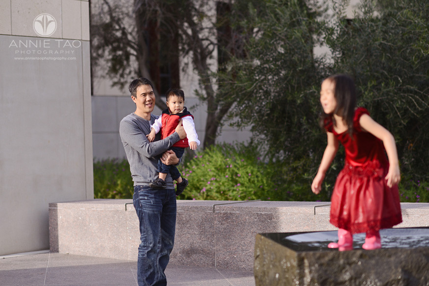 Bay-Area-Palo-Alto-lifestyle-family-photography-father-holding-baby-and-watching-daughter-in-fountain
