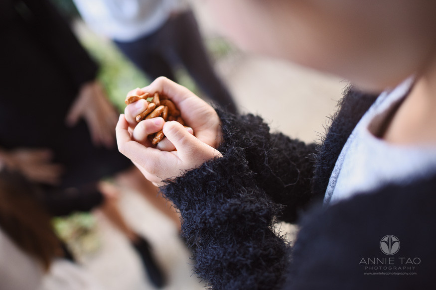 San-Francisco-lifestyle-children-photography-girl-grasping-fistful-of-pretzel-snacks-tightly
