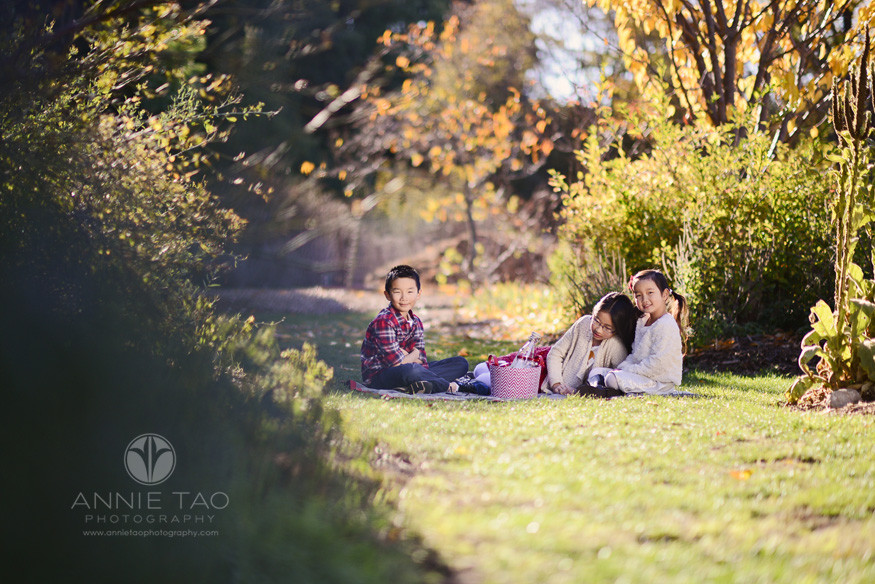 East-Bay-children-lifestyle-photography-three-laughing-sibling-children-hanging-out-on-picnic-blanket