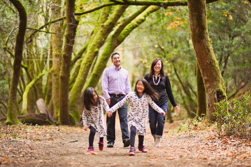 Bay-Area-lifestyle-family-photography-family-walking-together-in-magical-green-moss-lined-trees-focus-on-parents