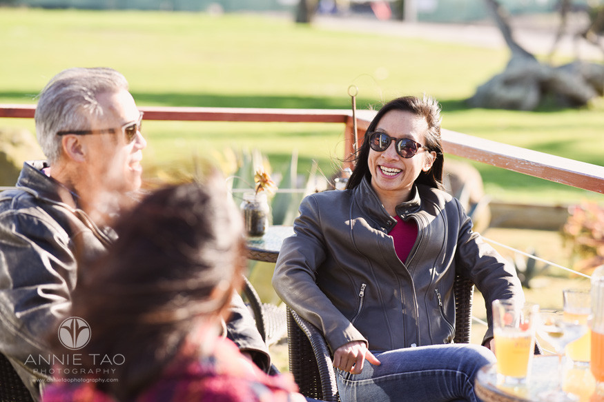 San-Francisco-lifestyle-family-photography-happy-woman-talking-with-parents-in-outdoor-patio