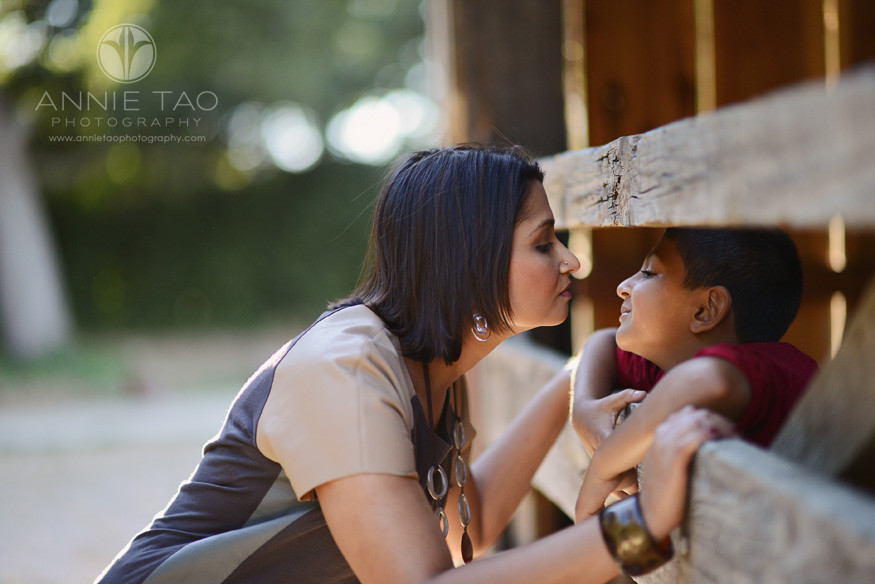 East-Bay-lifestyle-family-photography-mother-leaning-in-for-her-sons-kiss-through-barn-door