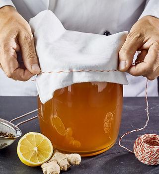 Man closing jar full of kombucha SCOBY t