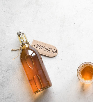Kombucha fermented drink in glass and bo