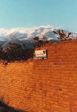 An alley in Tehran with a view of the Alborz Mountains, as depicted in the novel, Unrest.