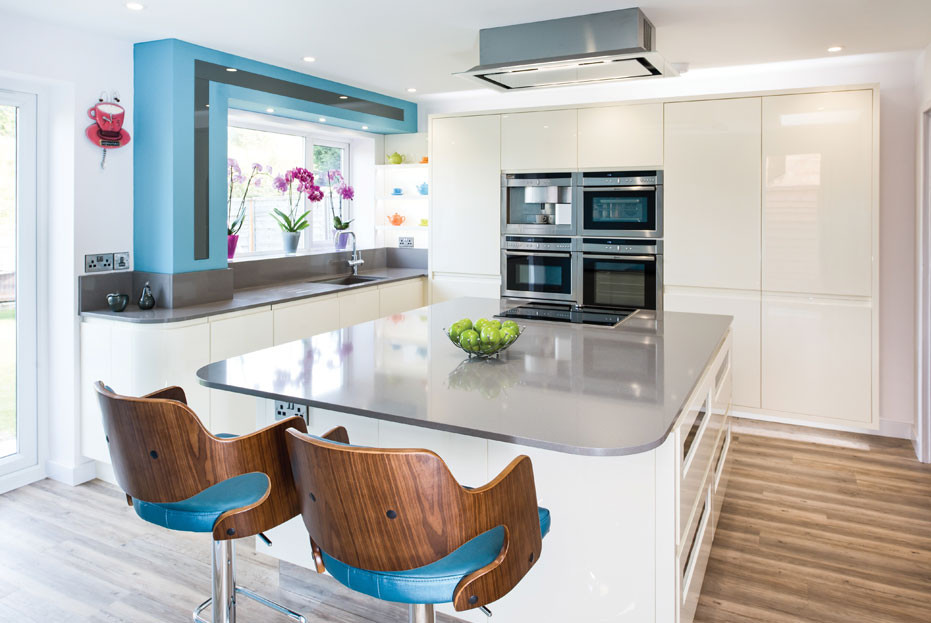 White gloss kitchen with blue stools and wall feature