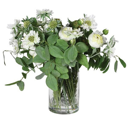 Glass vase with bouquet of eucalyptus , ranunculus and a variety  of cream flowe